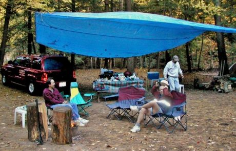 men under blue tarp at camping trip