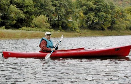 man kayaking in red kayak